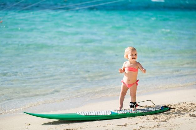 小さな女の赤ちゃんはサーフィンを学んでいます