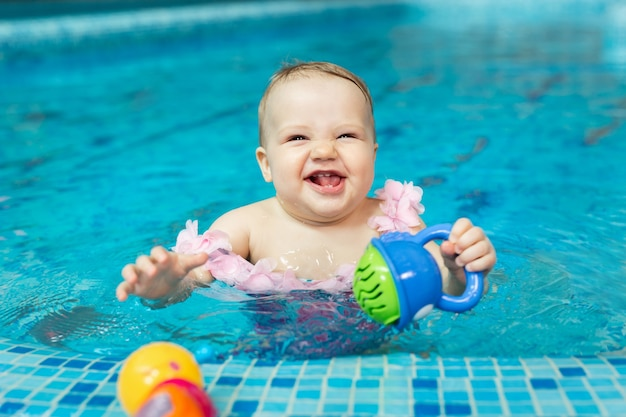 Little baby girl is playing with bright toys in the pool.