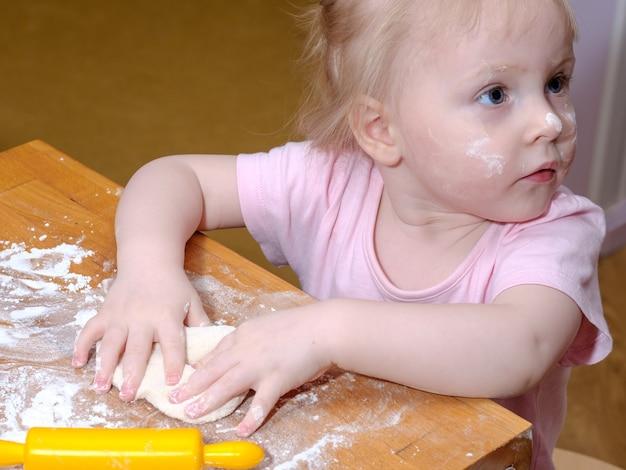 어린 소녀는 손과 롤링 핀으로 테이블에 반죽을 반죽한다