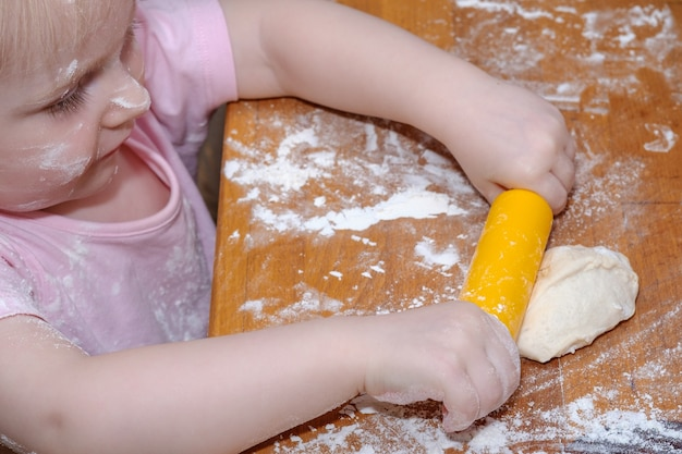 小さな女の赤ちゃんは、手とめん棒で木製のテーブルに生地をこねます。子供は自分でペストリーを作ることができることに満足しています。赤ちゃんの顔と小麦粉の服。幸せな子供時代。