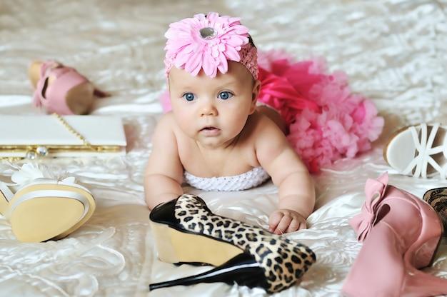 Маленькая девочка лежит на кровати и играет в модные туфли на каблуках