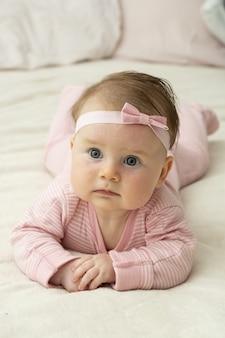 おなかを置く方法を学ぶ小さな女の赤ちゃん。
