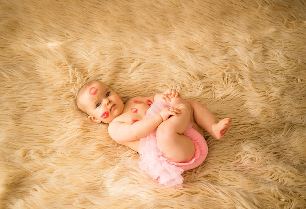 A little baby girl lies in pink panties with ruffles. there are traces of red kisses on the girl's body