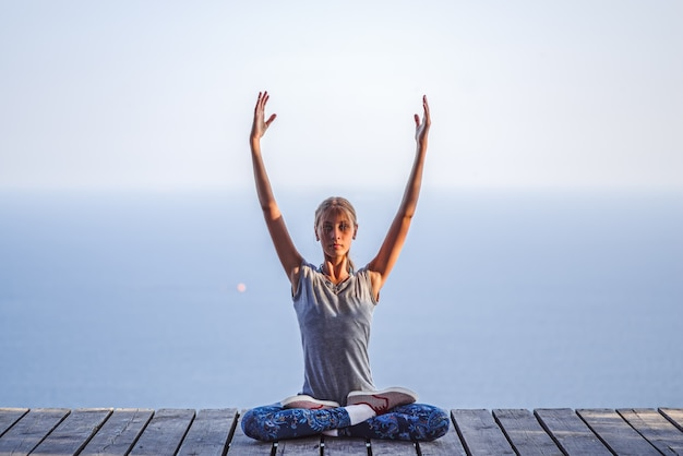 Little baby girl in lotus pose doing yoga exercises sitting on the roof of gazebo on sea