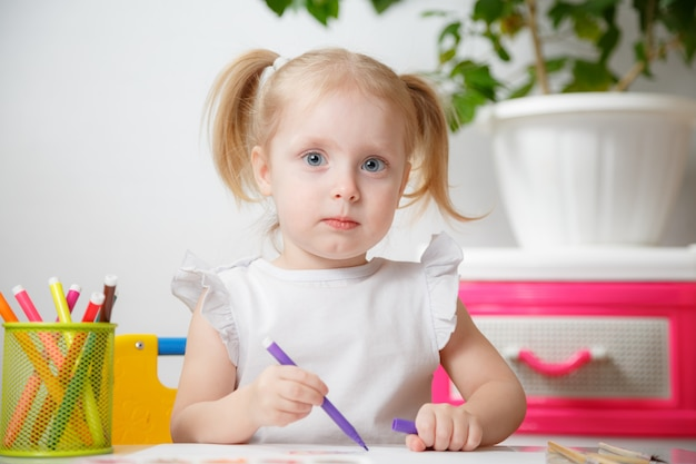 Little baby girl painting at table in home or kindergarten preschool. cute adorable small child with two pony tails drawing indoor.box with multicolored marker pens.