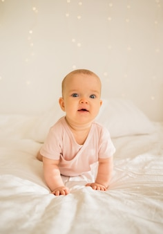 Little baby girl in pink bodysuit crawls on the bed
