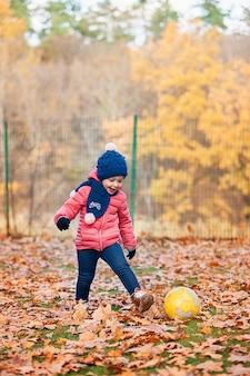 秋の紅葉で遊ぶ小さな女の赤ちゃん