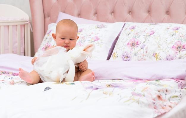 コピースペースのある保育園のベッドで大きなぬいぐるみで遊んでいる小さな女の赤ちゃん