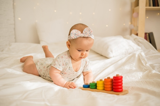 Little baby girl playing with an educational toy on the bed in the room.early child development