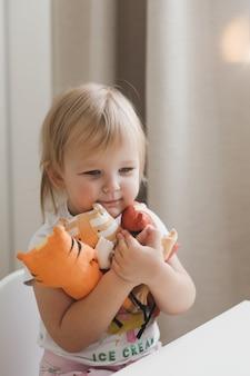 햇볕이 잘 드는 보육원에서 재미있는 작은 호랑이 장난감 상징을 가지고 노는 어린 소녀