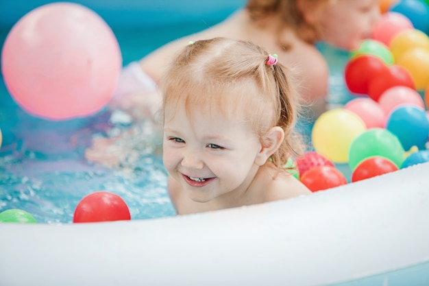 The little baby girl playing with toys in inflatable pool in the summer sunny day