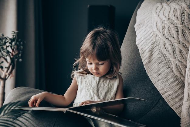 Маленькая девочка, читая книгу дома. она изолируется во время карантина