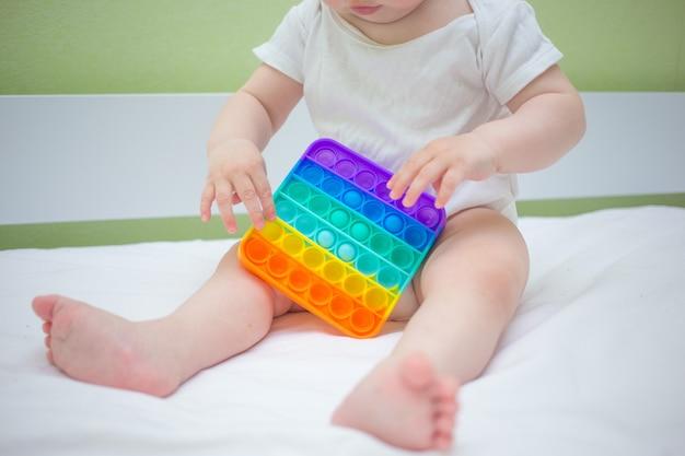 집에서 침대에 앉아 있는 어린 소녀가 아이들에게 인기 있는 팝-잇(pop-it) 새로운 스트레스 방지 장난감을 가지고 놀고 있습니다. 아이 개발 아이디어.