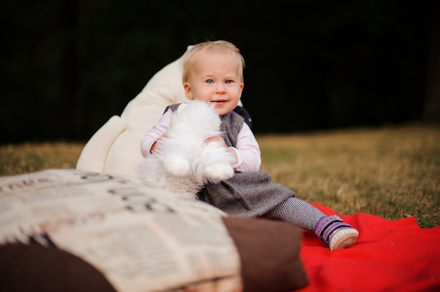 Little baby girl sitting on a blanket in the park