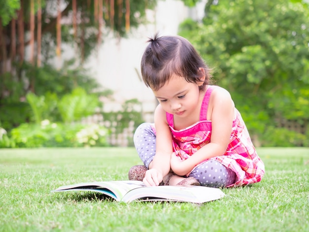 Little baby girl sitting on the grass in the garden and reading a picture book.