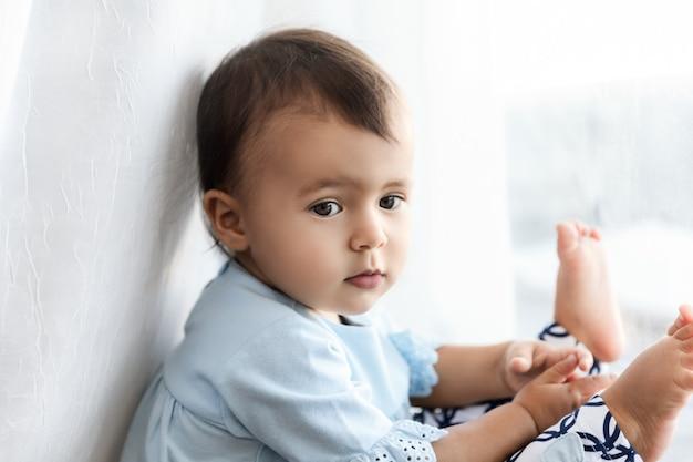 Маленькая девочка сидит у окна дома, образ жизни портрет