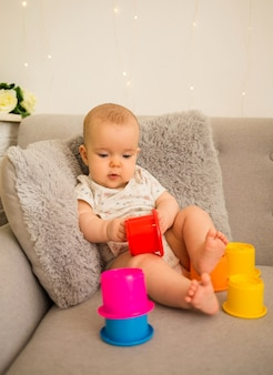 Little baby girl sitting on the sofa with a developing pyramid in the room
