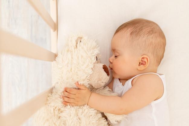 Маленькая девочка спит в белой кровати с мягким медведем, здоровый детский сон
