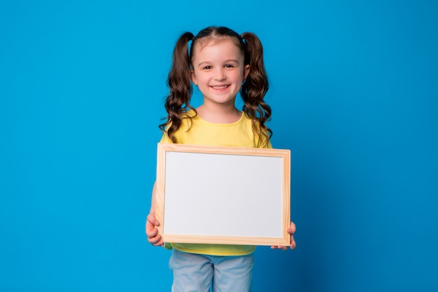 Little baby girl smiles and holds an empty drawing board on blue