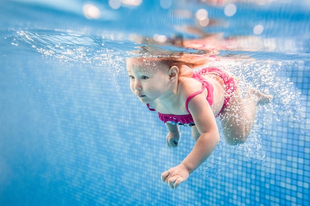小さな赤ちゃん、水泳プールで水の下で泳いでいる少女。ダイビング赤ちゃん。幼児の子供が泳ぐことを学ぶ。水泳と泡をお楽しみください。