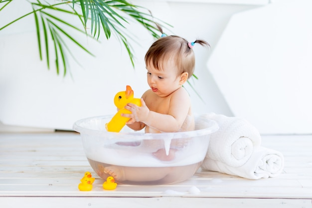 Little baby girl washes in a basin with foam