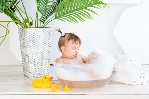 Маленькая девочка моется в тазу с пеной
