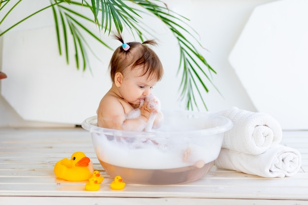 Little baby girl washes and plays in a basin with foam and water in a bright room at home
