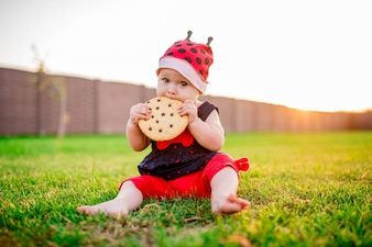 Little baby-girl with a large chocolate cookie sits on the back-yard