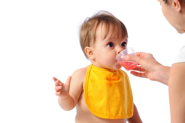 턱받이가 있는 어린 소녀가 카메라를 보고 컵에서 물을 마시거나 설탕에 절인 과일을 먹습니다.