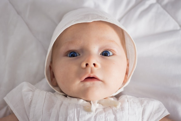 Little baby girl with blue eyes in white dress and hat on white blanket.