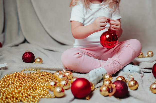 Little baby girl with christmas ornaments around.