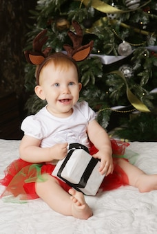 Little baby girl with the gift box near christmas tree.