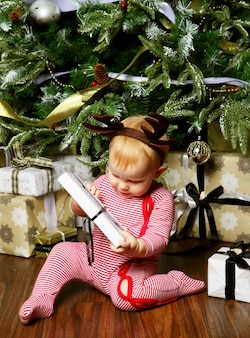 Little baby girl with the gift box near decorating christmas tree. happy time.
