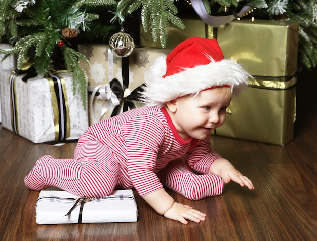 Little baby girl with the gift box near  decorating christmas tree