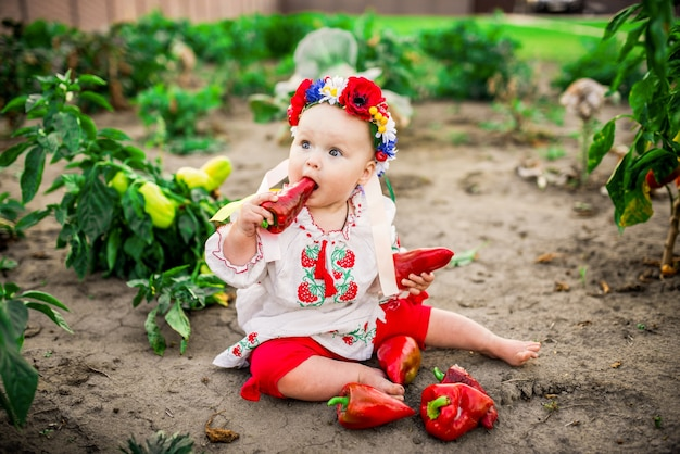 Little baby-girl with a large red pepper sits on the back-yard