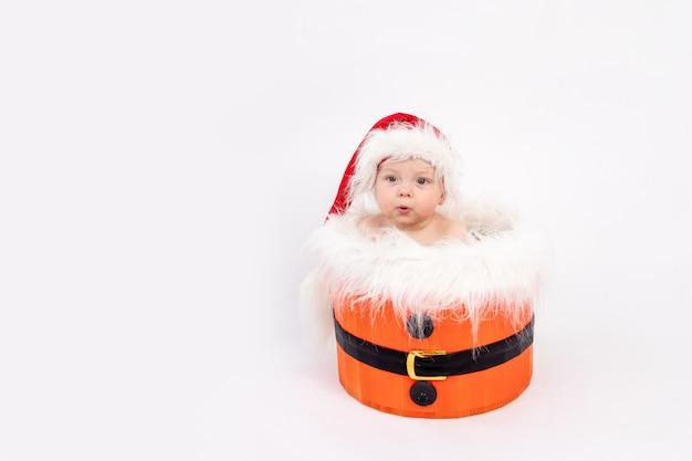バスケットに座っているサンタの帽子をかぶった小さな女の赤ちゃん