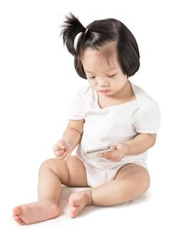 白で隔離されるスマートフォンで小さな女の赤ちゃん