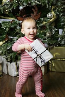 Маленькая девочка с подарочной коробке возле украшения елки