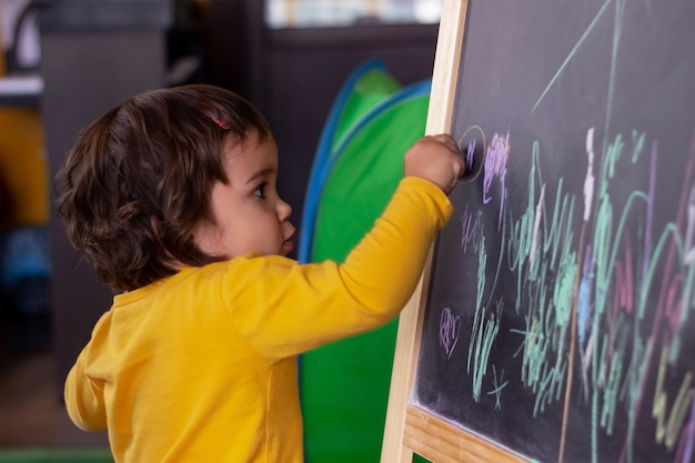 A little  baby girl in a yellow sweatshirt draws on a blackboard with colored crayons