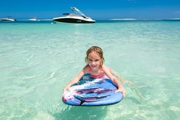 Маленькая девочка - молодой серфер с бодибордом развлекается на небольших океанских волнах. активный семейный образ жизни