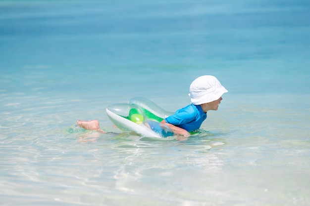 Little baby in hat on tropical beach swimming
