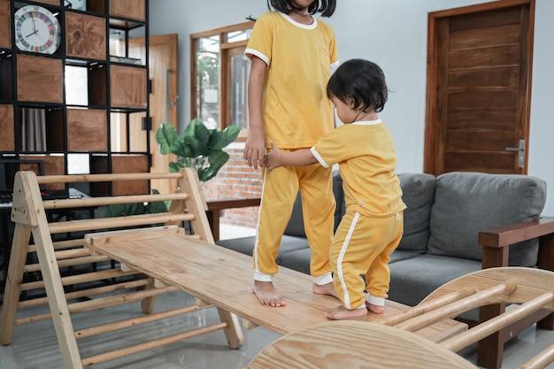 작은 아기는 pikler 삼각형 장난감에서 노는 동안 자매의 발을 잡고