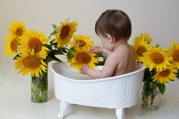 Маленький ребенок в ванне с цветами