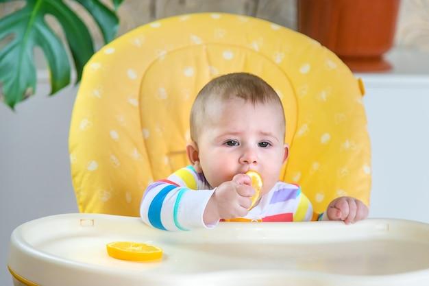 작은 아기가 레몬을 먹고 있습니다. 선택적 초점. 사람들.