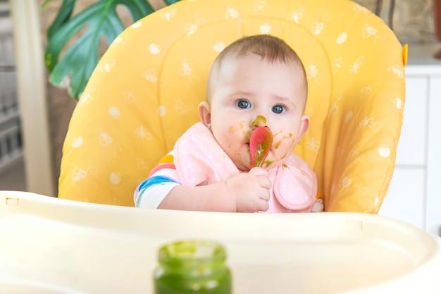 小さな赤ちゃんはブロッコリーの野菜のピューレを食べています。セレクティブフォーカス。人。