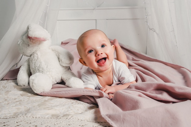 A little baby lays on a bed with a toy rabbit and smiles