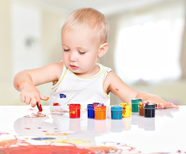 Little baby paint by his hands at home.