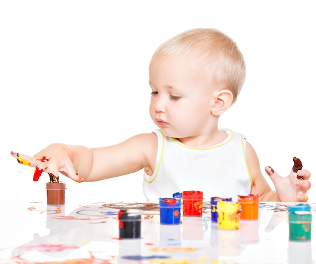 Little baby paint by his hands - on white wall.