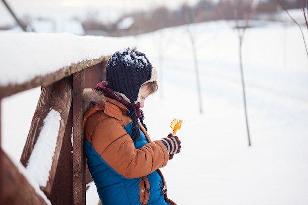 Little baby playing and eating sweet cockerel in winter day. kids play in snowy forest.