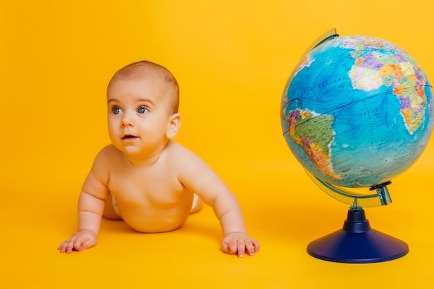 Маленький ребенок играет рядом с земным шаром